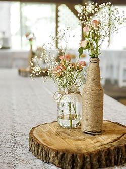 Centre de table avec pots, bouteille en verre et fleurs
